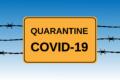 Schild auf Stacheldraht mit Text QUARANTINE COVID-19